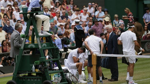 Umpire Damien Dumusois checks on Croatia's Marin Cilic as he receives treatment during the Men's Singles final match against Switzerland's Roger Federer, right, on day thirteen at the Wimbledon Tennis Championships in London Sunday, July 16, 2017. (AP Photo/Tim Ireland)