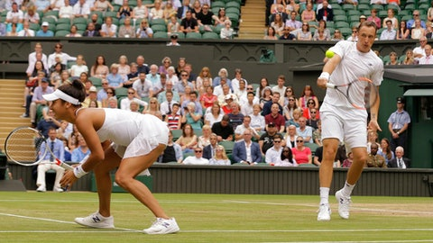 Finland's Henri Kontinen and Britain's Heather Watson return to Britain's Jamie Murray and Switzerland's Martina Hingis during the Mixed Doubles final match on day thirteen at the Wimbledon Tennis Championships in London Sunday, July 16, 2017. (AP Photo/Alastair Grant)