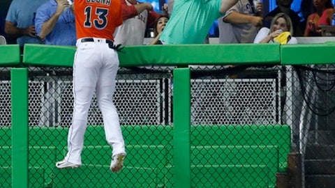 Miami Marlins left fielder Marcell Ozuna (13) climbs the fence as a fan attempts to catch a ball hit by Los Angeles Dodgers' Justin Turner for a home run, during the first inning of a baseball game, Sunday, July 16, 2017, in Miami. (AP Photo/Wilfredo Lee)