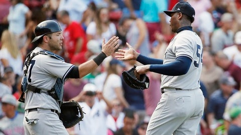 New York Yankees' Aroldis Chapman (54) and Austin Romine (27) celebrate after defeating the Boston Red Sox 3-0 in the first game of a baseball doubleheader in Boston, Sunday, July 16, 2017. (AP Photo/Michael Dwyer)