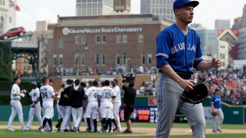 Toronto Blue Jays relief pitcher Lucas Harrell, foreground, walks off the field as the Detroit Tigers celebrate their winin the 11th inning of a baseball game, Sunday, July 16, 2017, in Detroit. (AP Photo/Carlos Osorio)