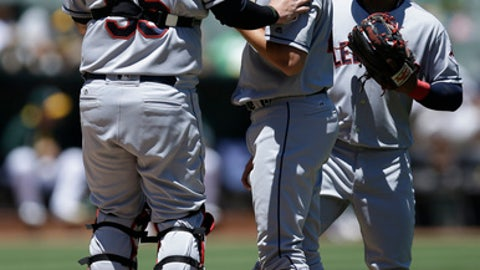 Cleveland Indians catcher Roberto Perez, left, speaks to pitcher Trevor Bauer, center, in the first inning of a baseball game against the Oakland Athletics, Sunday, July 16, 2017, in Oakland, Calif. (AP Photo/Ben Margot)