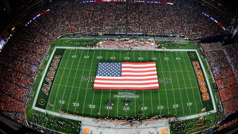 FILE - In this Jan. 11, 2016, file photo, an American flag is seen on the field during the national anthem before the NCAA college football playoff championship game between Clemson and Alabama, in Glendale, Ariz. The Atlantic Coast Conference has closed the gap on the Southeastern Conference with a four-year run that includes two national championships and two Heisman Trophy winners. Now the ACC and SEC look awfully similar, from their top tiers and divisional imbalances to their Southern-stronghold recruiting bases in overlapping geographic footprints. (AP Photo/Ross D. Franklin, File)