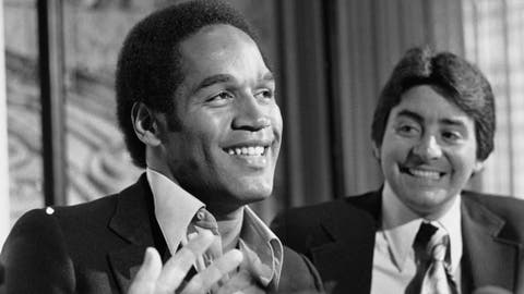FILE - In this March 24, 1978 file photo, O.J. Simpson, left, smiles next to San Francisco 49ers owner Edward DeBartolo Jr. at a news conference where the 49ers announced that Simpson had been traded to them from the Buffalo Bills, in San Francisco. Simpson, the former football star, TV pitchman and now Nevada prison inmate, will have a lot going for him when he appears before state parole board members Thursday, July 20, 2017, seeking his release after more than eight years for an ill-fated bid to retrieve sports memorabilia. (AP Photo/Sal Veder, file)