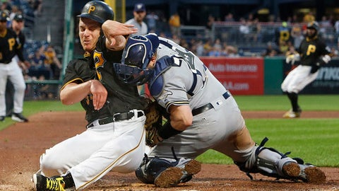 Pittsburgh Pirates' Chad Kuhl, left, collides with Milwaukee Brewers catcher Stephen Vogt during the fifth inning of a baseball game in Pittsburgh, Monday, July 17, 2017. Kuhl was out. Both players were shaken up on the play and Vogt left the game. (AP Photo/Gene J. Puskar)