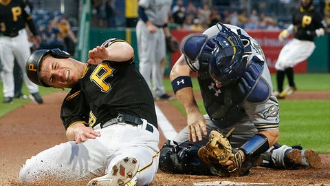 Pittsburgh Pirates' Chad Kuhl, left, reacts after a collision with Milwaukee Brewers catcher Stephen Vogt while being tagged out during the fifth inning of a baseball game in Pittsburgh, Monday, July 17, 2017. Both players were shaken up on the play and Vogt left the game. (AP Photo/Gene J. Puskar)
