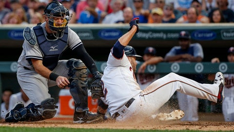 New York Yankees catcher Austin Romine tags out Minnesota Twins Brian Dozier during the third inning of a baseball game Monday, July 17, 2017, in Minneapolis. (AP Photo/Bruce Kluckhohn)