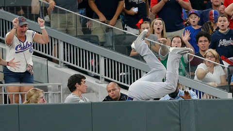 Chicago Cubs left fielder Kyle Schwarber goes over the wall to catch a foul ball by Atlanta Braves' Freddie Freeman during the sixth inning of a baseball game Monday, July 17, 2017, in Atlanta. (AP Photo/John Bazemore)