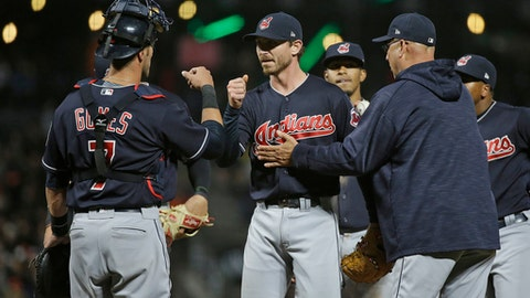 Cleveland Indians starting pitcher Josh Tomlin, center, is greeted by catcher Yan Gomes, left, and manager Terry Francona, right, while being removed during the eighth inning of the team's baseball game against the San Francisco Giants on Monday, July 17, 2017, in San Francisco. (AP Photo/Eric Risberg)