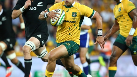 FILE - In this Oct. 18, 2014 file photo, Australia's Christian Leali'ifano, center, runs away from New Zealand's Richie McCaw, left, during the Bledisloe cup rugby match against New Zealand in Brisbane, Australia.  Leali'ifano has been selected on the reserves bench for the Brumbies in the Super Rugby playoffs, less than a year after being diagnosed with leukemia. Brumbies coach Stephen Larkham announced inside back Leali'ifano's comeback on Tuesday, July 18, 2017,  for their home quarterfinal in Canberra against the Wellington, New Zealand-based Hurricanes.  (AP Photo/Tertius Pickard, File)
