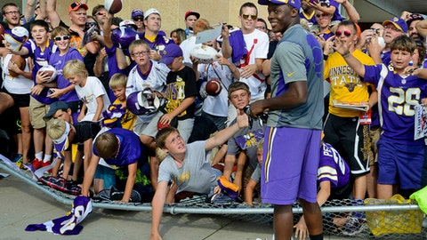 FILE - In this Aug. 14, 2014, file photo, a chain link fence collapses under the pressure of Minnesota Vikings fans trying to get Vikings rookie quarterback Teddy Bridgewater's glove after he tossed it to them on the last day of NFL football training camp for the team in Mankato, Minn. The Minnesota Vikings say the 52nd training camp in Mankato will be their last one away from headquarters. The Vikings announced on Tuesday that they plan to hold training camp at their new practice facility in the Twin Cities suburb of Eagan starting in 2018. (Ben Garvin/Pioneer Press via AP, File)