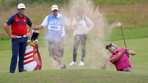 Spain's Jon Rahm, left, looks on as Spain's Sergio Garcia plays out of a bunker on the 5th hole during a practice round ahead of the British Open Golf Championship, at Royal Birkdale, Southport, England Wednesday, July 19, 2017. (AP Photo/Peter Morrison)