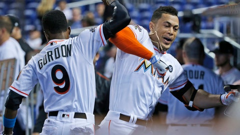 Miami Marlins' Giancarlo Stanton, right, celebrates with Dee Gordon (9) after Stanton hit a home run during the first inning of a baseball game against the Philadelphia Phillies, Wednesday, July 19, 2017, in Miami. (AP Photo/Wilfredo Lee)