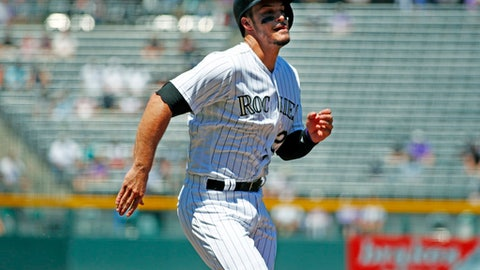Colorado Rockies' Nolan Arenado scores from third base on a sacrifice fly hit by Ian Desmond off San Diego Padres starting pitcher Clayton Richard in the first inning of a baseball game Wednesday, July 19, 2017, in Denver. (AP Photo/David Zalubowski)