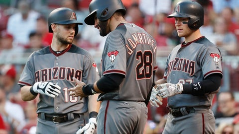 Arizona Diamondbacks' J.D. Martinez (28), center, winces in pain after after he was struck while swinging at a pitch from Cincinnati Reds starting pitcher Tim Adleman and taken out of the game in the fourth inning of a baseball game, Wednesday, July 19, 2017, in Cincinnati. (AP Photo/John Minchillo)