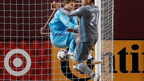 Minnesota United's Christian Ramirez (21) collides with Houston Dynamo goalie Tyler Deric during the second half of an MLS soccer match Wednesday, June 19, 2017, in Minneapolis. (Carlos Gonzalez/Star Tribune via AP)