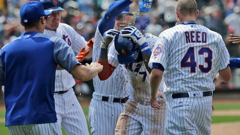 New York Mets' Jose Reyes, center, is mobbed by teammates after hitting a walk-off RBI single during the ninth inning of a baseball game against the St. Louis Cardinals at Citi Field, Thursday, July 20, 2017, in New York. The Mets defeated the Cardinals 3-2. (AP Photo/Seth Wenig)
