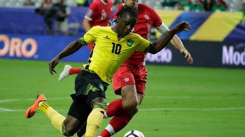 Jamaica's Darren Mattocks (10) dribbles past Canada's Dejan Jakovic during a CONCACAF Gold Cup quarterfinal soccer match, Thursday, July 20, 2017, in Glendale, Ariz. (AP Photo/Matt York)