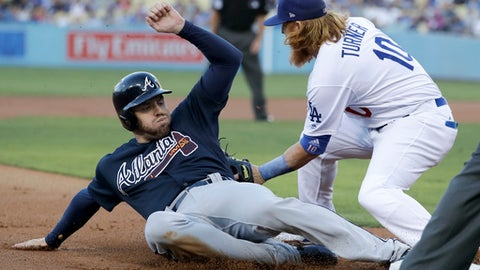 Atlanta Braves' Freddie Freeman is safe past Los Angeles Dodgers third baseman Justin Turner on a hit by Matt Kemp during the first inning of a baseball game in Los Angeles, Thursday, July 20, 2017. (AP Photo/Chris Carlson)