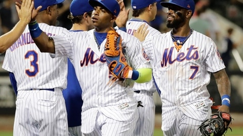 New York Mets' Yoenis Cespedes, center, and Jose Reyes, right, celebrate with teammates after an interleague baseball game against the Oakland Athletics, Friday, July 21, 2017, in New York. (AP Photo/Frank Franklin II)
