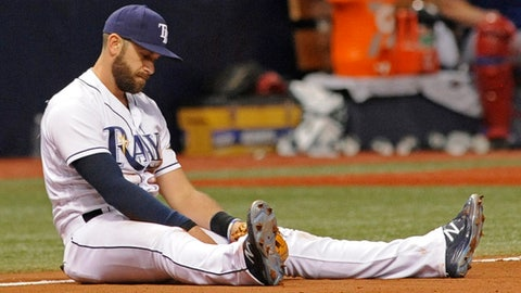 Tampa Bay Rays third baseman Evan Longoria sits in the dirt after making a diving catch but was unable to throw out Texas Rangers' Elvis Andrus out at first allowing the go-ahed run to score during the 10th inning of a baseball game Friday, July 21, 2017, in St. Petersburg, Fla. (AP Photo/Steve Nesius)