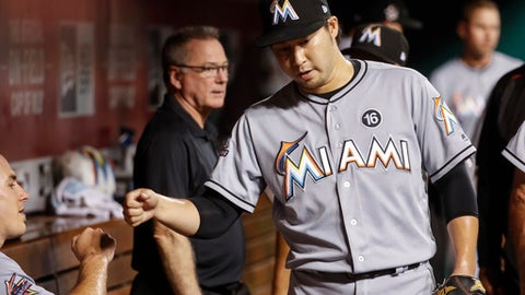 Miami Marlins relief pitcher Junichi Tazawa celebrates in the dugout after the seventh inning of the team's baseball game against the Cincinnati Reds, Friday, July 21, 2017, in Cincinnati. The Marlins won 3-1. (AP Photo/John Minchillo)