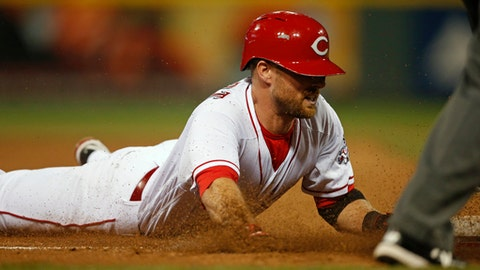 Cincinnati Reds' Zack Cozart slides into third base with a triple against the Miami Marlins during the fifth inning of a baseball game, Saturday, July 22, 2017, in Cincinnati. (AP Photo/Gary Landers)