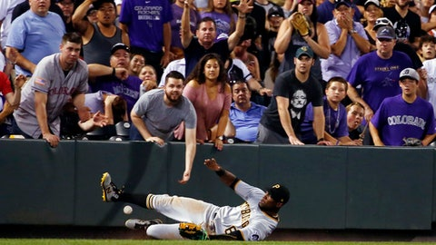Pittsburgh Pirates left fielder Starling Marte slides but misses a foul ball by the Colorado Rockies during the eighth inning of a baseball game Saturday, July 22, 2017, in Denver. (AP Photo/Jack Dempsey)