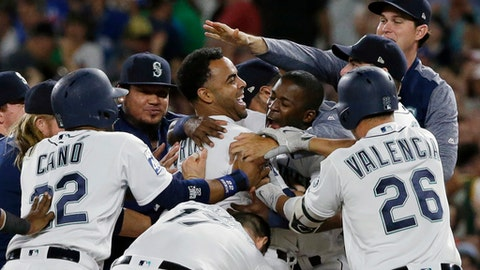 Seattle Mariners' Nelson Cruz, center, is mobbed by teammates after he hit a walk-off single to score Ben Gamel during the 10th inning of the team's baseball game against the New York Yankees, Saturday, July 22, 2017, in Seattle. The Mariners won 6-5. (AP Photo/Ted S. Warren)