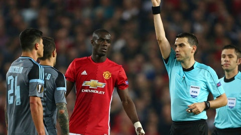 FILE - This is a Thursday, May 11, 2017 file photo of referee Ovidiu Hategan, second right, as he shows the red card and sends off both Manchester United's Eric Bailly, centre,  and Celta's Facundo Roncaglia, left, during the Europa League semifinal second leg soccer match between Manchester United and Celta Vigo at Old Trafford in Manchester, England.  UEFA said Monday July 24, 2017 that Manchester United defender Eric Bailly is suspended from the Super Cup game against Real Madrid and a Champions League group-stage game. UEFA's disciplinary panel imposed a three-match ban for violent conduct after Bailly was sent off late in Man United's Europa League semifinal, second-leg game against Celta Vigo in May. (AP Photo/Dave Thompson/File)