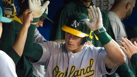 Oakland Athletics Matt Chapman gets high fives in the dugout after hitting a solo home run against the Toronto Blue Jays in the first inning of a baseball game in Toronto, Monday, July 24, 2017. (Fred Thornhill/The Canadian Press via AP)