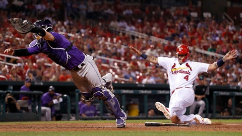 Colorado Rockies catcher Tony Wolters, left, dives for the throw from Rockies' Mark Reynolds as St. Louis Cardinals' Yadier Molina, right, scores during the eighth inning of a baseball game Monday, July 24, 2017, in St. Louis. Reynolds was charged with a throwing error on the play (AP Photo/Jeff Roberson)