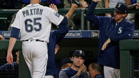 Seattle Mariners starting pitcher James Paxton (65) is greeted at the dugout after he got out of a jam to end the seventh inning of a baseball game against the Boston Red Sox, Monday, July 24, 2017, in Seattle. (AP Photo/Ted S. Warren)