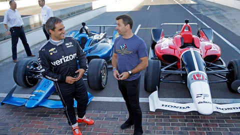 Two-time Indianapolis 500 winner Juan Pablo Montoya, left, and Spanish driver Oriol Servia talk in front of the newly-designed IndyCars at the Indianapolis Motor Speedway, Tuesday, July 25, 2017, in Indianapolis.  (AP Photo/Michael Conroy)