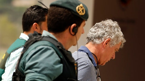 FILE - A Tuesday, July 18, 2017 file photo showing former President of the Spanish Football Federation, Angel Maria Villar, right, as he is lead by Spanish Civil Guard policeman to enter the Federation headquarters during an anti-corruption operation in Las Rozas, outside Madrid. Spain's highest sports authority has suspended the president of the Spanish football federation a week after he went to jail following his arrest in an anti-corruption investigation. (AP Photo/Francisco Seco, File)