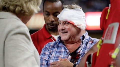 A fan is helped from the stands after being hit by a foul ball during the eighth inning of a baseball game between the New York Yankees and the Cincinnati Reds on Tuesday, July 25, 2017, in New York. (AP Photo/Frank Franklin II)