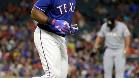 Texas Rangers' Adrian Beltre jogs to first after earning a walk from Miami Marlins relief pitcher Hunter Cervenka, rear, during the fifth inning of a baseball game, Tuesday, July 25, 2017, in Arlington, Texas. (AP Photo/Tony Gutierrez)
