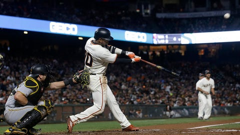San Francisco Giants' Eduardo Nunez hits a two-run double in front of Pittsburgh Pirates catcher Francisco Cervelli during the fourth inning of a baseball game in San Francisco, Tuesday, July 25, 2017. (AP Photo/Jeff Chiu)
