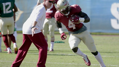 FILE - In this Dec. 27, 2016, file photo, Florida State running back Dalvin Cook (4) runs as head coach Jimbo Fisher looks on during NCAA college football practice in Fort Lauderdale, Fla. The two-a-day football practices that coaches once used to toughen up their teams and cram for the start of the season are going the way of tear-away jerseys and the wishbone formation. (AP Photo/Lynne Sladky, File)
