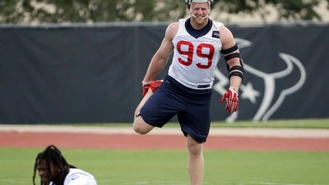 FILE - In this Tuesday, June 6, 2017 file photo, Houston Texans defensive end J.J. Watt (99) stretches during an NFL organized team activities football practice in Houston. A year after missing all of the preseason on his way to an injury-shortened and frustrating regular season, J.J. Watt made his return to training camp for the Houston Texans on Wednesday, July 26, 2017. (AP Photo/David J. Phillip, File)