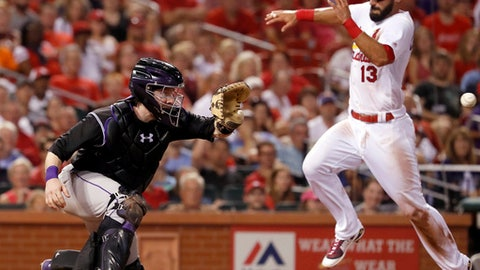 St. Louis Cardinals' Matt Carpenter (13) scores past Colorado Rockies catcher Ryan Hanigan during the fourth inning of a baseball game Wednesday, July 26, 2017, in St. Louis. (AP Photo/Jeff Roberson)