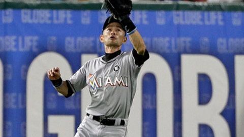 Miami Marlins right fielder Ichiro Suzuki reaches up to secure a sacrifice fly by Texas Rangers' Carlos Gomez that scored Mike Napoli during the sixth inning of a baseball game, Wednesday, July 26, 2017, in Arlington, Texas. (AP Photo/Tony Gutierrez)