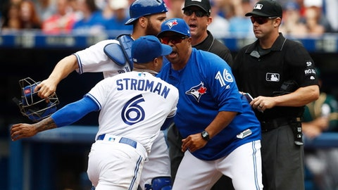 Toronto Blue Jays bench coach DeMarlo Hale (16) tries to hold back pitcher Marcus Stroman (6) and catcher Russell Martin (55) after they were ejected by umpire Will Little, right, during the fifth inning of a baseball game against the Oakland Athletics in Toronto on Thursday, July 27, 2017.  (Mark Blinch/The Canadian Press via AP)