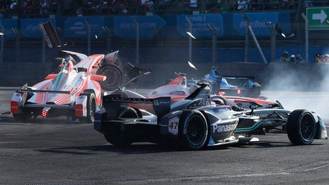 FILE - A Saturday, April 1, 2017 file photo of Mahindra Racing driver Nick Heidfeld, left, crashing with his teammate Felix Rosenqvist, past Panasonic Jaguar Racing driver Adam Caroll, front, during the Formula E Mexico City ePrix auto race, in Mexico City. Ahead of the Formula E series ending this weekend in Montreal, Canada, the two traditional racing giants, Mercedes and Porsche, have announced that they will compete in the series from 2019.  (AP Photo /Marco Ugarte, File)