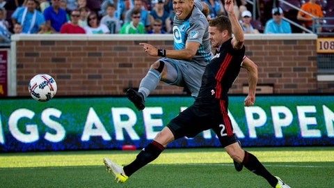 Minnesota United's Christian Ramirez, left, scores a goal while D.C. United's Taylor Kemp attempts to block during the first half of an MLS soccer game Saturday, July 29, 2017, in Minneapolis. (Courtney Pedroza/Star Tribune via AP)