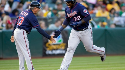 Minnesota Twins' Miguel Sano (22) shakes hands with third base coach Gene Glynn after hitting a two-run home run off Oakland Athletics' Chris Smith during the fifth inning of a baseball game on Saturday, July 29, 2017, in Oakland, Calif. (AP Photo/D. Ross Cameron)