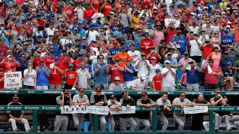 The Baltimore Orioles stand at the top of the dugout as they and fans watch Texas Rangers' Adrian Beltre during his at-bat int he second inning of a baseball game, Sunday, July 30, 2017, in Arlington, Texas. Beltre is one hit away from his 3,000th career hit. (AP Photo/Tony Gutierrez)