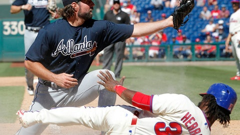 Atlanta Braves' pitcher R.A. Dickey shows the ball to home plate umpire Pat Hoberg, not pictured, after tagging out Philadelphia Phillies' Odubel Herrera trying to score on a wild pitch during the sixth inning of a baseball game against the Atlanta Braves, Sunday, July 30, 2017, in Philadelphia. (AP Photo/Tom Mihalek)