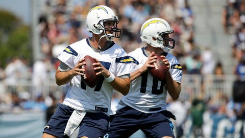 Los Angeles Chargers quarterback Philip Rivers, left, and Kellen Clemens pull back to throw a pass at an NFL football training camp, Sunday, July 30, 2017, in Costa Mesa, Calif. (AP Photo/Jae C. Hong)