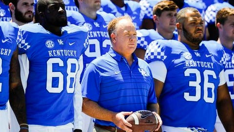 Kentucky head coach Mark Stoops stands with players during the team photo during an NCAA college football media day in Lexington, Ky., Sunday, July 30, 2017. (Alex Slitz/Lexington Herald-Leader via AP)